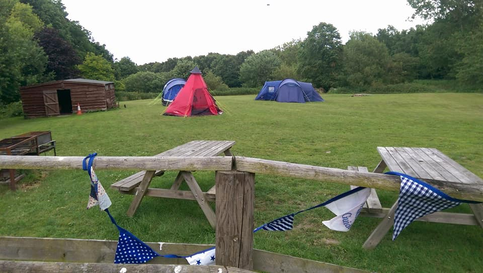 Picnic tables in the foreground, tents and the toilet block in the background showing the whole field as seen from the hut